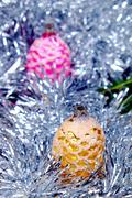 Christmas ornament in the shape of cones in pink and gold around her chain in Stock Photos
