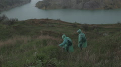 Two people in raincoat walking in quarry at rainy summer day Stock Footage