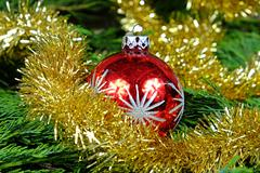Red Christmas ball with silver stars around her christmas chain in gold color - stock photo