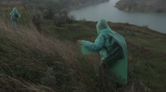 Two people in raincoat walking in quarry at rainy summer day - stock footage