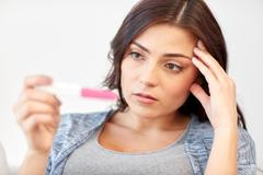 sad woman looking at home pregnancy test - stock photo