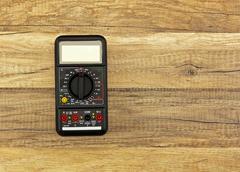 Digital multimeter on wooden floor, measure, control Stock Photos