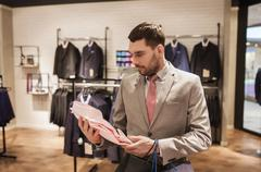 man with bags choosing shirt in clothing store - stock photo