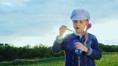 Girl 5 years of blowing bubbles. It is on the green meadow, the sun shines and Stock Footage