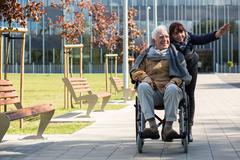 Retiree sitting in a wheelchair - stock photo