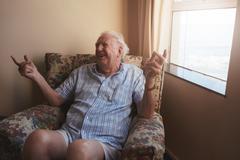 Senior man sitting in a arm chair Stock Photos