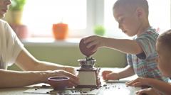 Twin brothers helping her mother to grind coffee Stock Footage