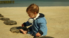 Lovely baby with headphone sits at the beach - stock footage