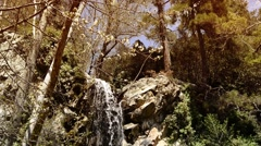 Small waterfall in the mountains among the flowering trees - stock footage