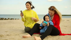 Family spending time with baby, sitting at the beach Stock Footage