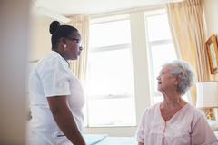 Female doctor visiting  patient for routine checkup - stock photo