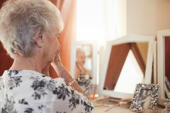 Senior woman getting ready at dresser - stock photo