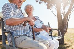 Senior couple sitting on a bench with walking stick Stock Photos