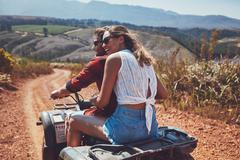 Young happy couple cruising on a quad vehicle Stock Photos
