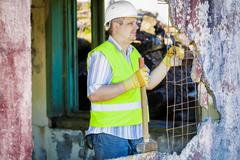 Construction worker with sledgehammer near demolished wall - stock photo