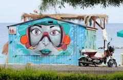 Garage door with street graffiti with woman face at public beach,Limassol,Cyprus - stock photo