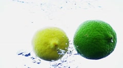 Lemon and lime dropping into water in slow motion. Stock Footage