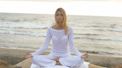 Detail of blond young woman sit on the rock during meditation - stock footage