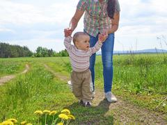 Mom teaches walks young son. - stock photo