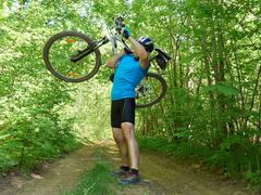 Cyclist man carries bicycle in green forest in summer. Stock Photos