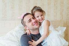Cute little girl with her father wearing crowns Stock Photos