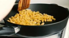 Wooden shovel stirs macaroni in a frying pan - stock footage