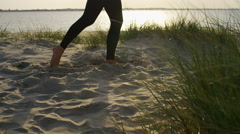 4K Young woman in a yoga warrior pose on a  beach, in slow motion - stock footage