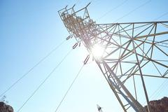 Electricity transmission tower against sun Stock Photos