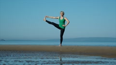 young pretty woman doing yoga on the beach in the afternoon - stock footage