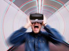 Man wearing virtual reality goggles., standing in corridor - stock photo