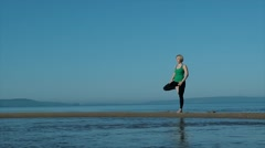 Young pretty woman doing yoga on the beach in the afternoon Stock Footage