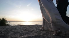 Couple expexting baby walking on a river shore holding hands on sunset - stock footage