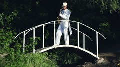 Saxophonist in a white frock coat and hat playing on the bridge. Stock Footage