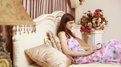 Young attractive beautiful woman, girl, reading a book, laying in a luxury bed - stock footage
