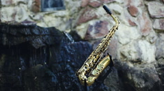 Saxophone. Musical instrument set against the backdrop of a waterfall. Stock Footage