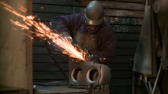 Metallurgical industrial factory: an man deburring a piece. Stock Footage