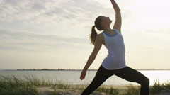 4K Young woman goes from a warrior pose into upward facing dog, in slow motion  Stock Footage