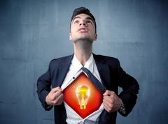 Businessman ripping off shirt and idea light bulb appears - stock photo