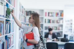 Famale student selecting book to read in library Stock Photos