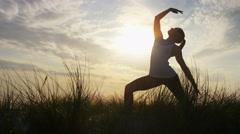 4K Silhouette female in a warrior yoga pose at sunset, in slow motion Stock Footage