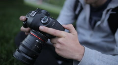 Young Photographer Adjusts The Digital SLR Camera Stock Footage