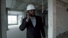 Young african architect goes through the premises of repaired building, talking Stock Footage