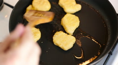 Hand with a wooden spatula to prevent frying chicken nuggets - stock footage