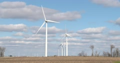 Group of Wind Turbines - Blue Sky, Brown Field - 4k Stock Footage