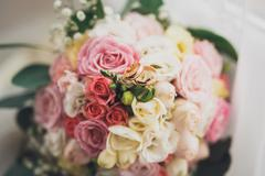 Pretty good wedding bouquet of various flowers with rings - stock photo
