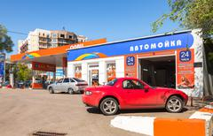Cars standing in line at the car wash near the gas station Olvi in sunny day Stock Photos