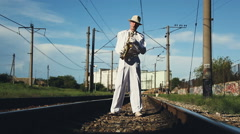 Saxophonist, male, middle-aged man standing on the railway sleepers. Series. - stock footage