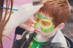 Child face painting process at redhead boy - stock photo