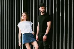 Stylish and fashionable couple posing metal fence - stock photo