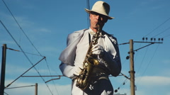 Saxophonist, male, middle-aged man standing on the railway sleepers. Series. Stock Footage